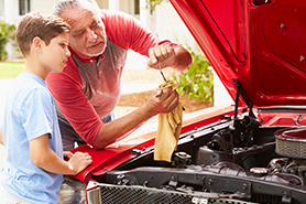 Grandfather working on car with grandson
