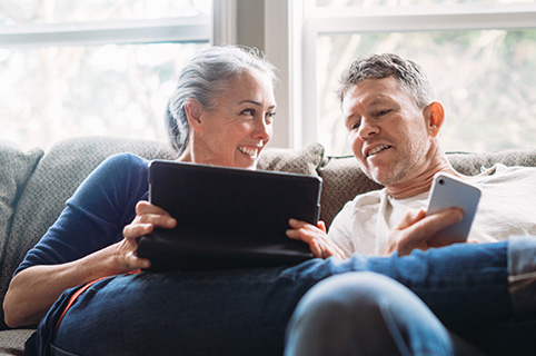 Man and woman with tablet and cell phone