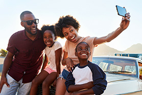 Smiling family taking a picture in front of their car